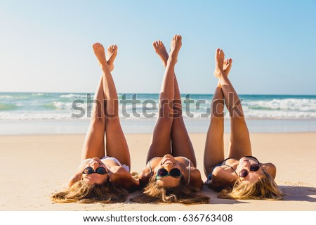 Three beautiful girls on the beach lying on the sand
