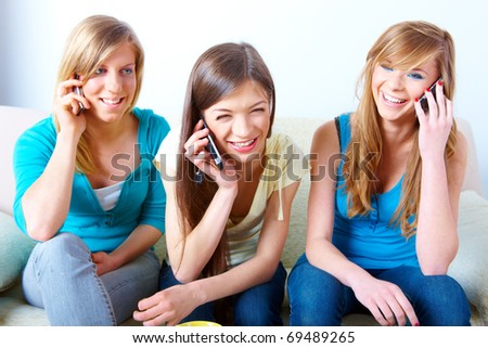 Three beautiful girls sitting on sofa in home and using their mobile phones.