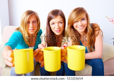 Three beautiful girls sitting on sofa in home with yellow cups