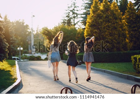 Three beautiful girls walking in the summer sunny city with coffee #1114941476