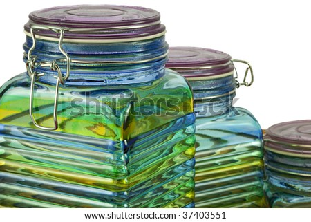 Three beautiful green, yellow and blue glass canisters or storage jars  isolated on white background