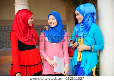 Three beautiful muslim girls having fun talking each other