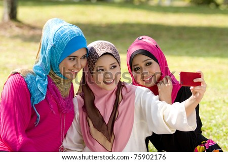 three beautiful muslim girls with red cellphone camera - stock photo