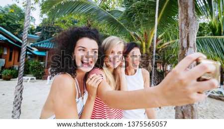 Three beautiful slender happy girlfriends students take selfie against the backdrop of a tropical resort, vacation and travel vacations in hot countries #1375565057