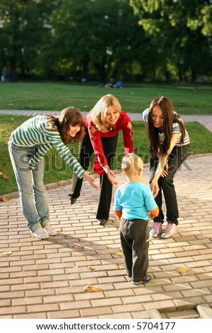 Three beautiful woman playing with a small boy.