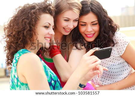 three beautiful women smiling while looking on a smart-phone