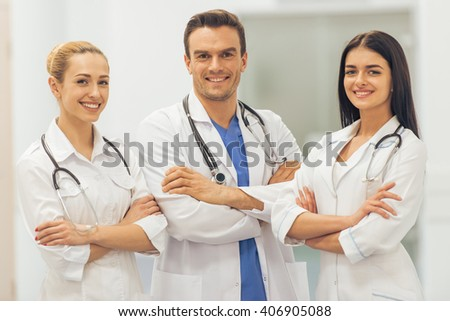 Three beautiful young doctors are looking at camera and smiling, standing with crossed arms in hall of the hospital