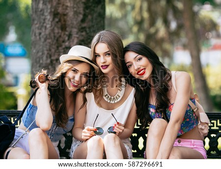 Three beautiful young girls posing against the backdrop of the park #587296691