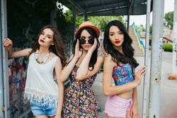 Three beautiful young girls posing at the bus stop