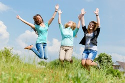 Three beautiful young ladies holding hands jumping on summer field outdoors background