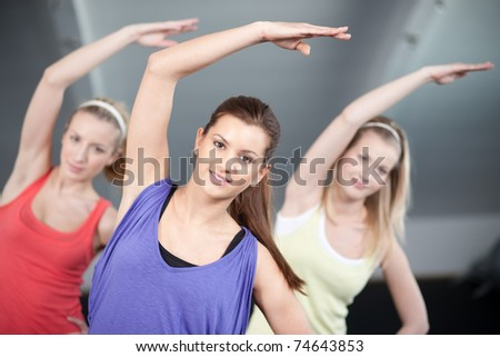 Three beautiful young woman doing aerobics exercises