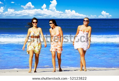 Three beautiful young woman on a tropical island beach on a sunny summer day
