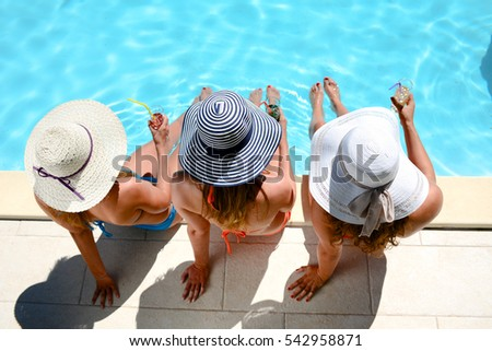 three beautiful young woman with sun hat sitting by the poolside of a resort swimming pool during summer holiday #542958871