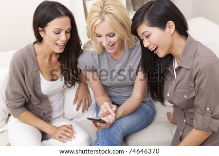 Three beautiful young women friends at home using a smart phone and laughing