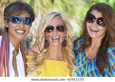 Three beautiful young women in their twenties laughing and having fun on vacation, shot in golden sunshine in a tropical resort location.