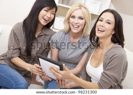 Three beautiful young women or girl friends at home using tablet computer and laughing