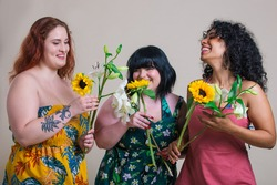 Three beautiful young women posing together and having fun. Concept about body positivity and self acceptance