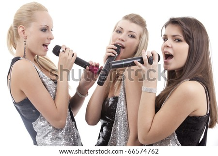 Three beautiful young women singing in microphones