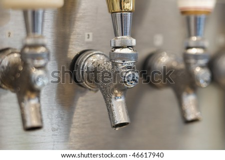 Three beer tap spouts with condensation showing at the openings. Horizontal shot. - stock photo