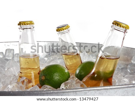 Three beers on ice with two limes