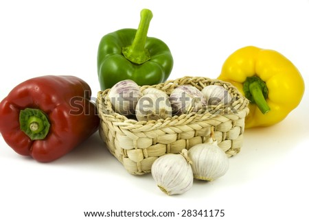 Three bell peppers and basket full of fresh garlics isolated on white background