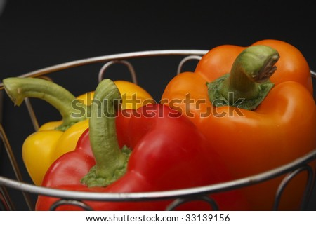 three bell peppers in chrome basket - stock photo