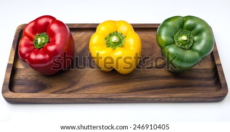 three Bell Peppers of colors shown in tray and isolated on white background / three Bell Peppers, red, yellow and green