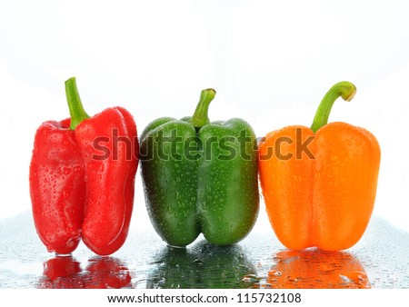 Three bell peppers, Red, Green, and Orange on a wet surface with reflections. Horizontal format.