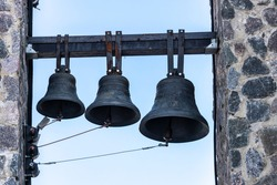 three bells hang on the bell tower of the Christian church. High quality photo