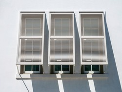 Three Bermuda shutters propped open by three windows of building with whitewashed wall on a sunny morning in the Florida Panhandle