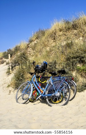 Three bicycles parked against sand dunes by the beach