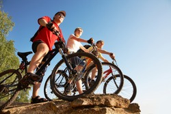 Three bicyclists on the brink of a rock look afar from rock breakage at beautiful lake