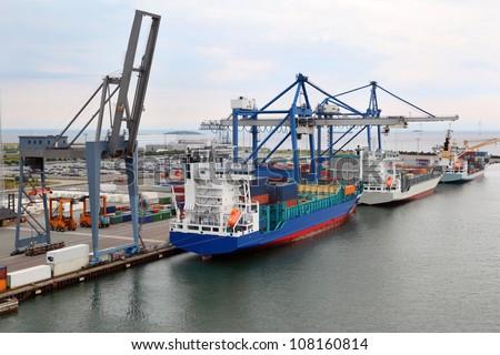 Three big cargo ships in Copenhagen seaport, Denmark; Cranes load cargo #108160814