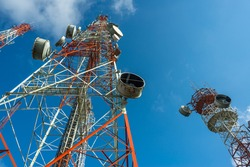 Three big radio mast attached with many dishes with blue sky