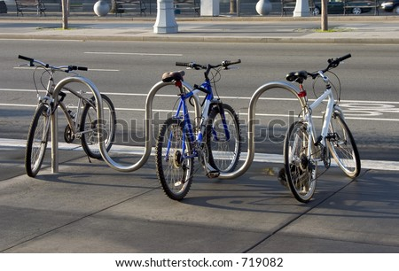 Three bikes are locked to a modern looking sidewalk rack.  The brand names and logos have been removed from all parts of the bikes.