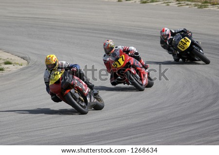 Three Bikes Coming out of a Turn at a Race