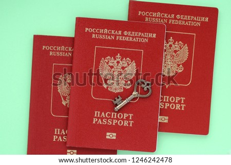 Three biometric passport citizen of the Russian Federation and small key on green background. Prohibited from leaving the country. Refusal of the visa