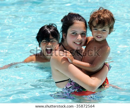 Three biracial siblings having fun in a community swimming pool.