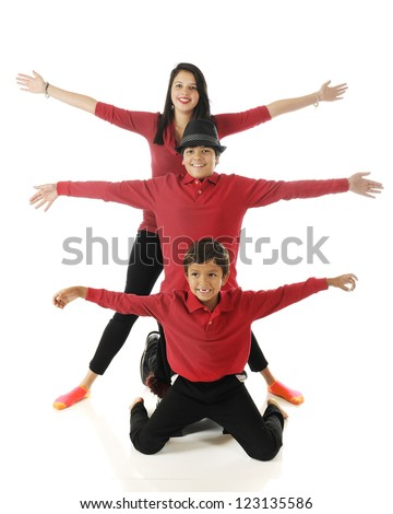 "Three biracial siblings stacked behind each other with their arms outstretched, like a 3-headed bug with 6 ""legs."" - stock photo"