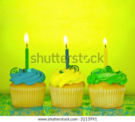 Three birthday cupcakes in blue, green, and yellow with lit candles, confetti, and sprinkles on a mirrored background - stock photo
