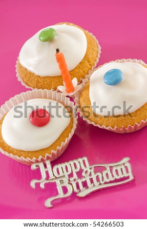 Three birthday iced buns with a candle