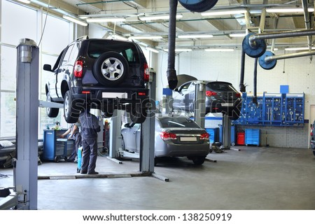Three black cars stand in small service station and two men repair one car.