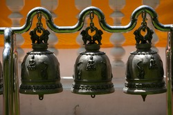 three black metal bell hanging in the buddhist temple