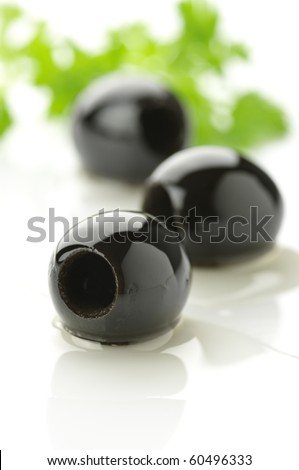 Three black olives in pool of oil on white background.