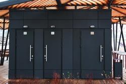 three black public toilet doors on the street