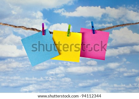 Three blank colorful notes clipped on twine clothesline with cheerful clothespins in front of beautiful blue sky