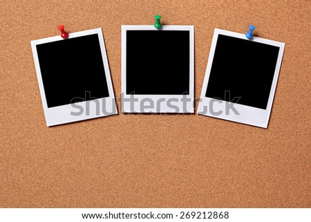 Three blank instant photo print, pushpin, cork background.