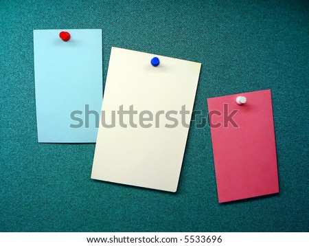 three blank memos posted on the wall of a modular office cubicle