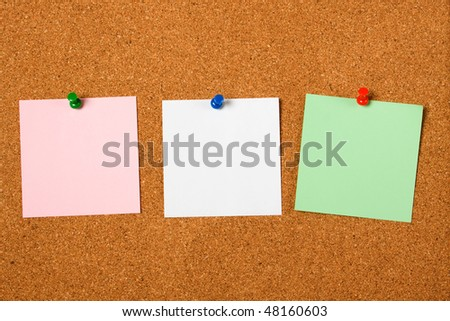 Three blank notes pinned on cork notice board