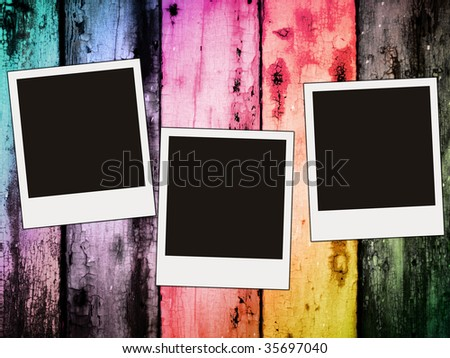 three blank photos on colorful wooden background